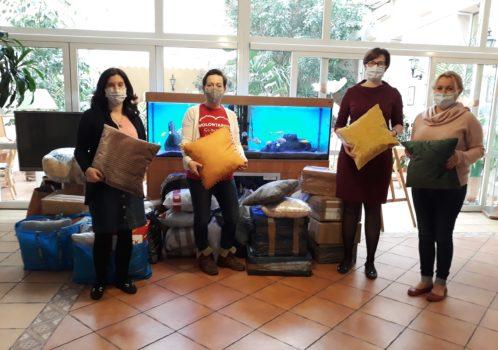 Zdjęcie z prezentami przy akwarium - moment przekazania poduszek oraz materiałów do terapii dla DPS