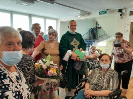 """Grupa mieszkańców Domu Pomocy Społecznej """"Chemik"""" pozująca do zdjęcia wraz z żegnanym księdzem, który trzyma w dłoniach prezent."""