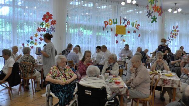 """Mieszkańcy DPS """"Chemik"""" siedzący przy stolikach w czasie piknikowego poczęstunku."""