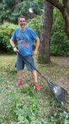 Uśmiechnięty Mężczyzna z grabiami w ręku, podczas prac ogrodowych.