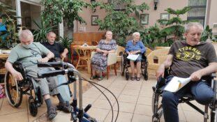Grupa mieszkańców DPS siedząca przy stolikach z tekstami piosenek w dłoniach.