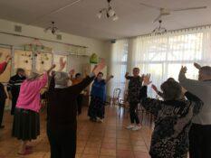 Grupa Mieszkańców wraz z instruktorem uchwyceni podczas poruszania się po okręgu z uniesionymi rękoma.