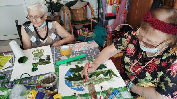 Dwie kobiety przy stole w pracowni plastycznej tworzą prace z wykorzystaniem farb i fragmentów roślin.